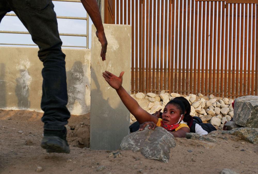 Мигрантка из Гаити пролезает под пограничной стеной США в Юме, штат Аризона