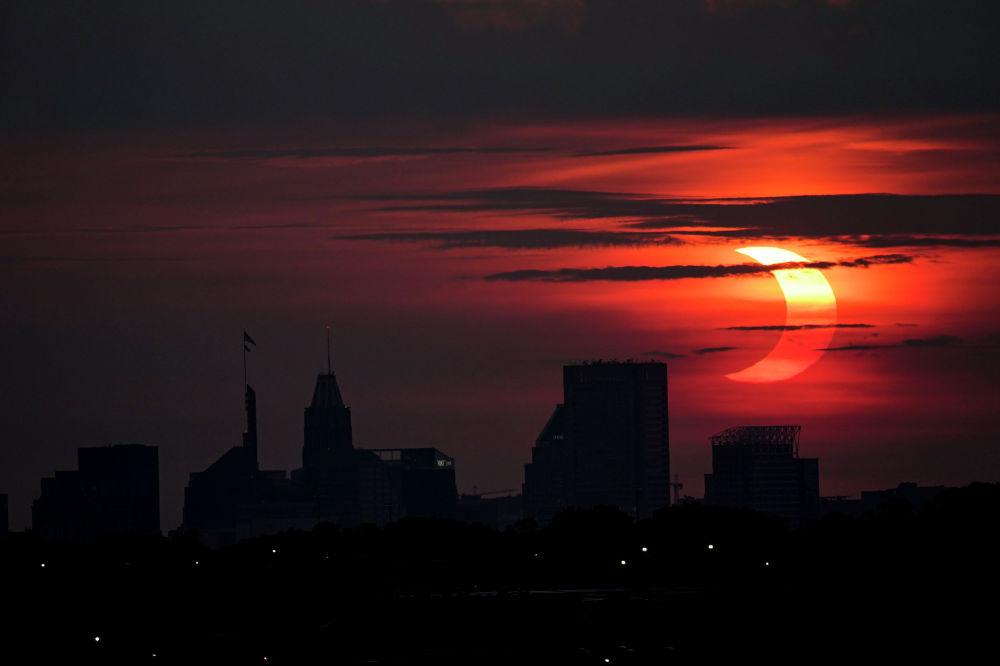 Частичное солнечное затмение над горизонтом Балтимора в штате Мэриленд. США 10 июня 2021 года
