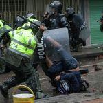 Офицер полиции бьет дубинкой демонстранта во время столкновений на антиправительственной акции в Боготе