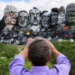 Мужчина фотографирует работу скульпторов сделанное из электронных отходов, изображающее лидеров G7 перед саммитом G7 в Корнуолле (Великобритания)