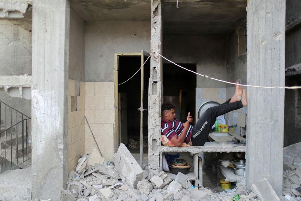 Палестинец в разрушенном бомбардировками доме в секторе Газа