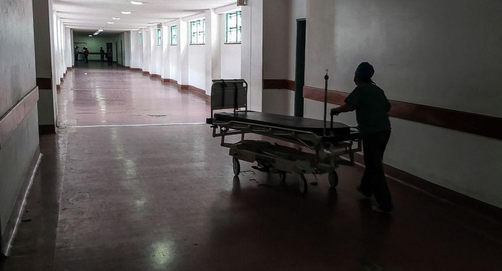 Медицинский работник перемещает каталку в коридоре больницы. Архивное фото