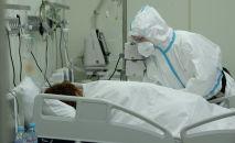 Медик ухаживает за пациентом с COVID-19 в больнице. Архивное фото