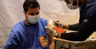 Мужчина получает вакцину от COVID-19 во временном пункте вакцинации в Нью-Йорке. Архивное фото