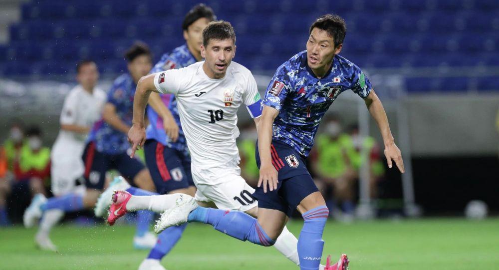 Футболисты сборной Кыргызстана и сборной Японии во время матча, в рамках отборочного тура к Чемпионату мира-2022 в Суйте (Япония)