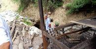 Люди и сотрудники МЧС на месте обвала шахты в селе Маркай Сузакского района