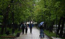 Прохожие гуляют по скверу во время дождливой погоды. Архивное фото