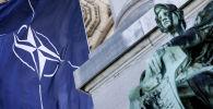 Флаг НАТО рядом со статуей во время саммита 2021 в Брюсселе. 13 июня 2021 года