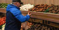 Мужчина покупает овощи в магазине. Архивное фото