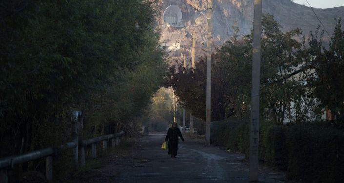 Пожилая женщина на улице на фоне горы Сулайман-Тоо в Оше