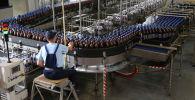 Работник у конвейера упаковки готовой пивной продукции. Архивное фото