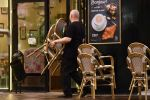 Сотрудник кафе на убирает мебель с уличной веранды