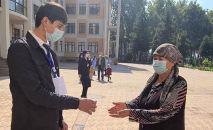 Женщине обрабатывают руки антисептиком в Душанбе. Архивное фото