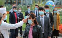 Медицинский персонал измеряет температуру людей в Душанбе. Архивное фото