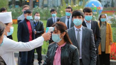 Душанбе шаарында медициналык кызматкерлери кишилердин температурасын өлчөп жатышат. Архив