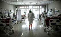 Медицинский сотрудник проверяет пациентов с COVID-19 в отделении интенсивной терапии больницы