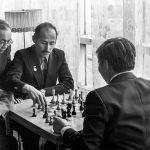 Шахмат ойногон Чокморов менен анын каршылашына көз салган жаш Думанаев