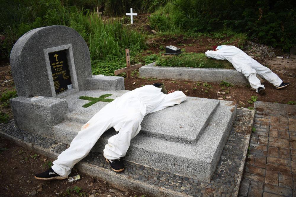Могильщики отдыхают во время перерыва на кладбище для жертв коронавируса в Бандунге, Индонезия. 15 июня 2021 года