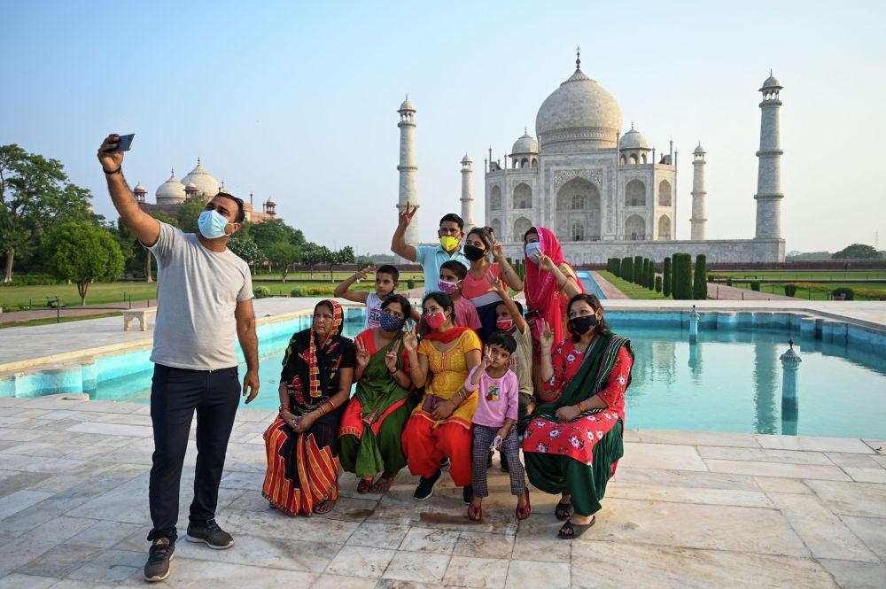 Группа туристов фотографируются в Тадж-Махале после того, как он снова открыт для посетителей в Агре, Индия. 16 июня 2021 года