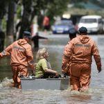 Сотрудники МЧС России эвакуируют женщину за затопленном районе в Керчи.