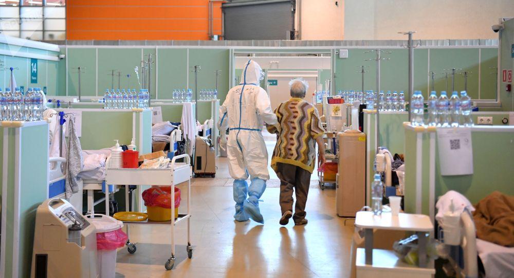 Медицинский работник и пациент в палате в госпитале COVID-19