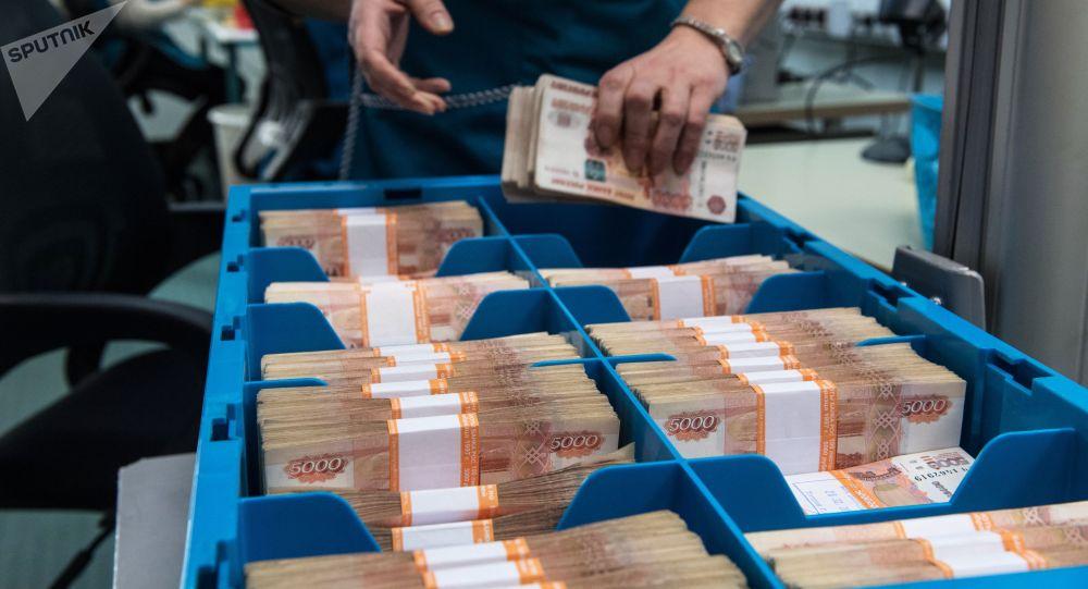 Сотрудница банка загружает деньги в бокс. Архивное фото