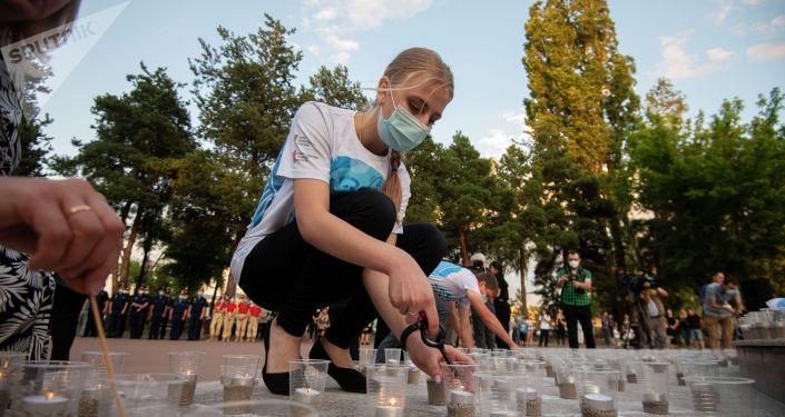 Участник акции Свеча памяти зажигает свечи в Бишкеке, приуроченные к 80-летию начала Великой Отечественной войны