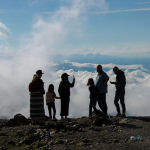 Люди на фоне верблюжего перевала Тоо-Ашуу окутанного облаками