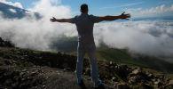Мужчина раскинув руки стоит на фоне верблюжего перевала Тоо-Ашуу окутанного облаками