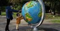 Ребенок и женщина в масках смотрят на гигантский глобус в Ухане. Архивное фото