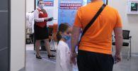 Мужчина с ребенком стоят в очереди в прививочный пункт. Архивное фото