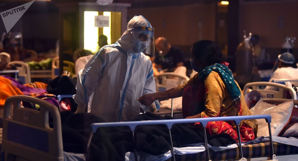 Медицинский работник оказывает помощь пациенту госпиталя в Дели.