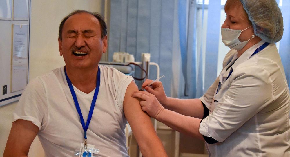 Министр здравоохранения Кыргызстана Алымкадыр Бейшеналиев получает вакцину Sinopharm. Архивное фото