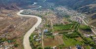 Вид с высоты на жилые дома и реку в городе Нарын.
