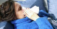 Женщина с симптомами гриппа лежит на диване. Иллюстративное фото