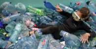Активист лежит в надувном бассейне, наполненном пластиковыми бутылками во время акции протеста. Архивное фото
