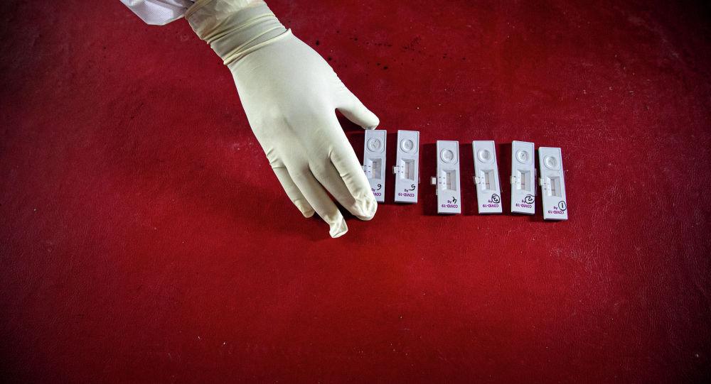 Медициналык кызматкер COVID-19га текшерүү үчүн үлгүлөрдү алып жатат. Архив