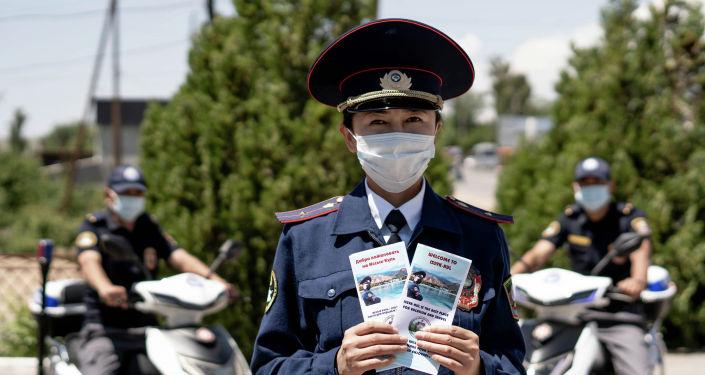 Сотрудник туристической милиции Иссык-Кульской области с брошюрами