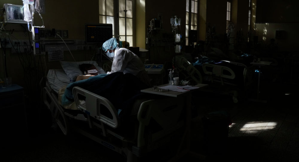 Медицинский работник оказывает помощь пациенту с COVID-19 в больнице. Архивное фото