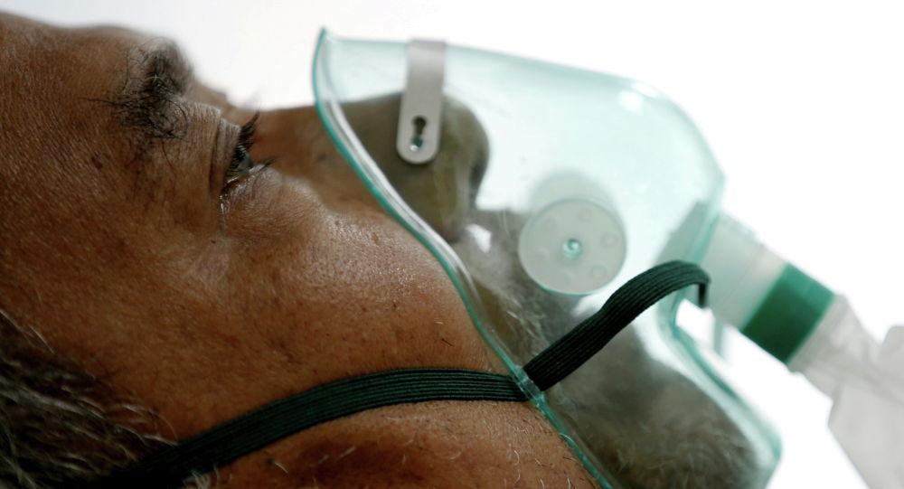 Пациент, страдающий коронавирусной болезнью (COVID-19), дышит в маске  в изоляторе больницы в Богоре. Индонезия, 26 января 2021 года