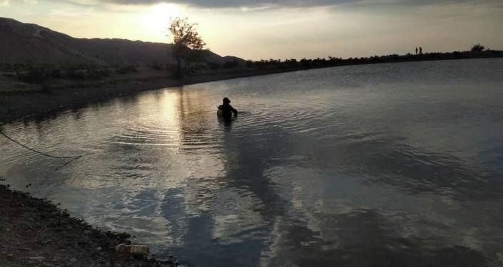 Сотрудник МЧС во время поисков утонувших девушек в Ысык-Атинском районе в пруду села Эпкин