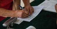 Женщина на избирательном участке в школе №24 в Бишкеке во время повторных выборов депутатов в БГК