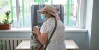 Пожилая женщина на избирательном участке в школе