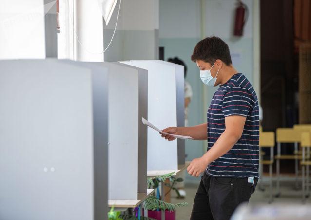 Парень на избирательном участке в школе №24 в Бишкеке во время повторных выборов депутатов в БГК. 11 июля 2021 года