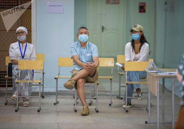 Наблюдатели на избирательном участке в школе №24 в Бишкеке во время повторных выборов депутатов в БГК. 11 июля 2021 года