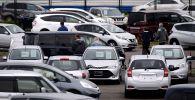 Люди осматривают автомобили, выставленные на продажу. Архивное фото