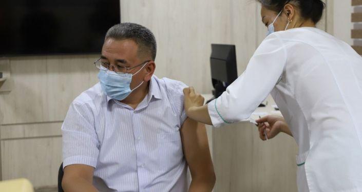 Заместитель министра внутренних дел Эркебек Аширходжоев во время вакцинации от коронавируса