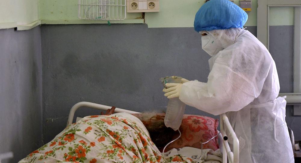 Медсестра, одетая в СИЗ (средства индивидуальной защиты), ухаживает за пациентом с коронавирусной инфекцией Covid-19. Архивное фото