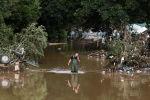Мужчина идет по воде в районе, пострадавшем от наводнения после проливных дождей в Бад-Нойенар-Арвайлере