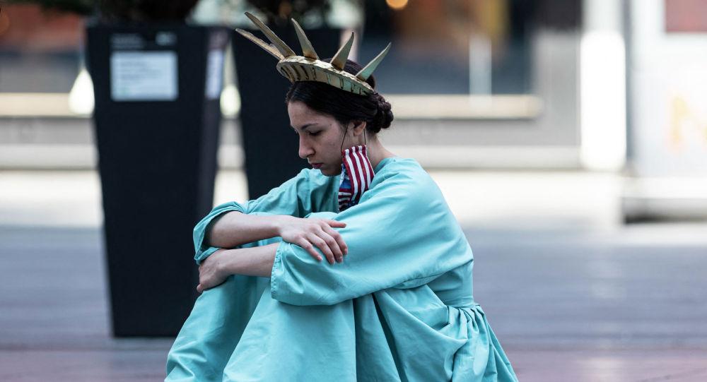 Девушка в костюме Статуи Свободы сидит на Таймс-сквер в Нью-Йорке. Архивное фото